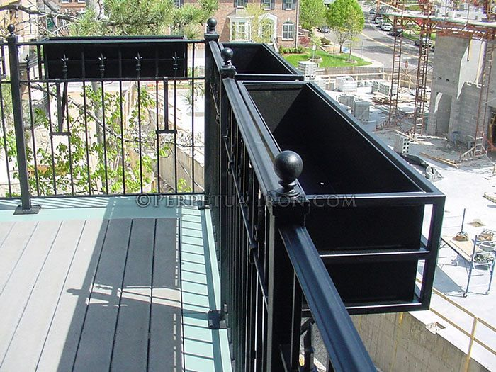 A fabricated steel flower box hanging on a balcony railing ...